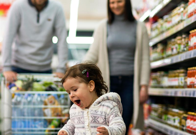 Parents grocery shopping with child